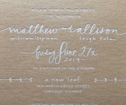 Wedding invitation in white foil, on tan chip board.